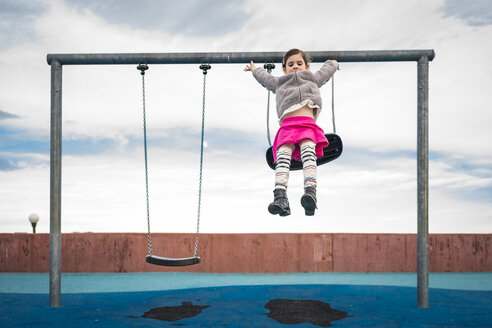 Playful girl jumping on sand from swing against cloudy sky at playground - CAVF49377