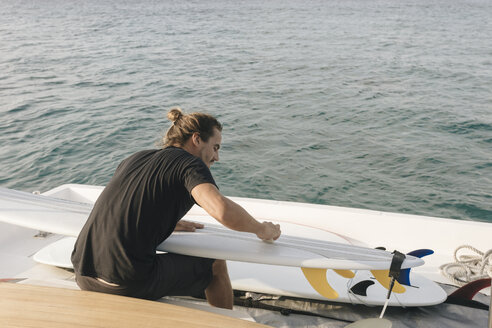 Rear view of man cleaning surfboard while sitting in yacht on sea - CAVF49383
