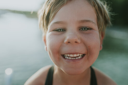 Close-up portrait of happy girl against lake - CAVF49392