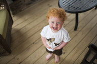 High angle portrait of happy cute baby boy standing on hardwood floor at home - CAVF49398