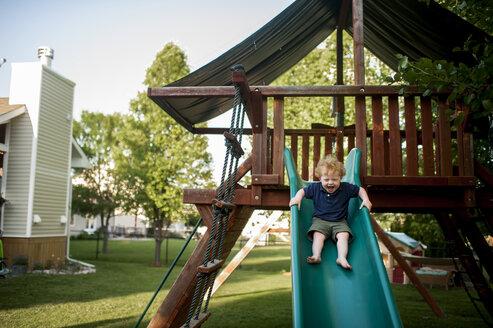 Happy baby boy screaming while sliding at yard - CAVF49401