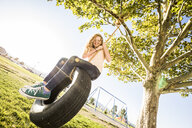 Low angle portrait of smiling girl sitting on tire swing at park during sunny day - CAVF49416