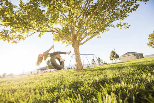 Carefree girl swinging on tire swing hanging from branch at park during sunny day - CAVF49422