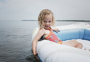 Portrait of cute girl sitting in inflatable raft on lake against sky - CAVF49431