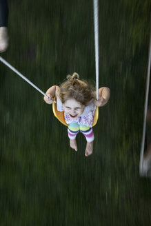 High angle view of happy girl swinging at park - CAVF49440