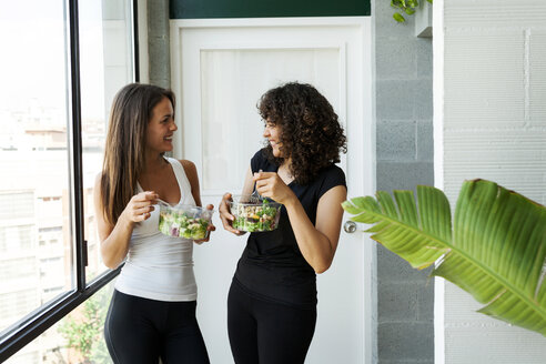 Happy female friends talking while eating salad by window at home - CAVF49452