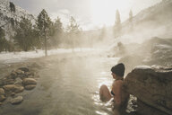 Side view of woman wearing bikini while sitting in thermal pool at forest during winter - CAVF49520
