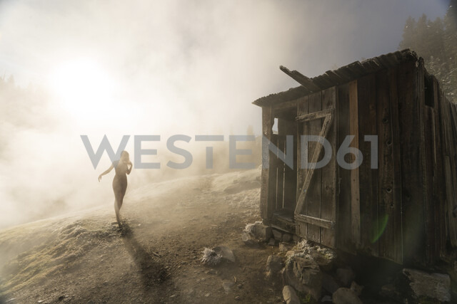 Silhouette woman walking towards old wooden hut on mountain during foggy weather - CAVF49523