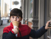Boy looking up while eating ice cream on footpath in city - CAVF49529