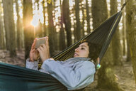 Woman using mobile phone while lying on hammock in forest during sunset - CAVF49547