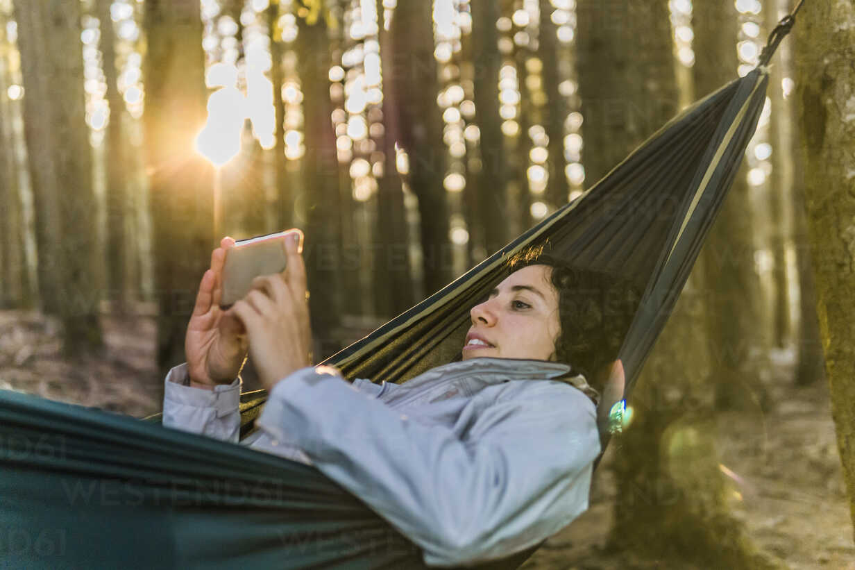 Woman using mobile phone while lying on hammock in forest during sunset - CAVF49547 - Cavan Images/Westend61