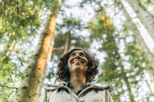 Low angle view of happy woman looking away while standing in forest - CAVF49550