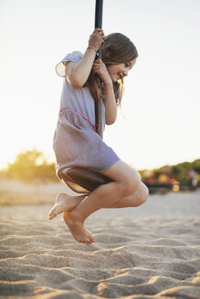 Happy girl swinging at playground against clear sky during sunset - CAVF49559