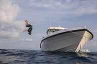 Low angle view of man diving into sea from yacht against cloudy sky at Maldives - CAVF49589