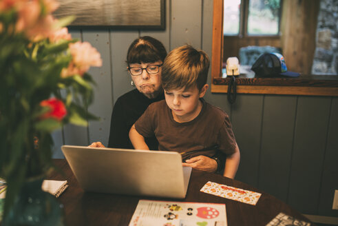 Grandson teaching grandmother to use laptop computer on table at home - CAVF49592