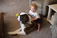 High angle portrait of cute happy baby boy sitting on dog at home - CAVF49598