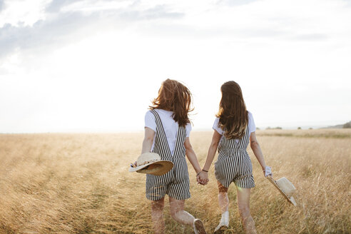 Rear view of happy twin sisters holding hands while walking on grassy field against sky during sunset - CAVF49610