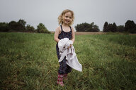 Portrait of happy girl holding fabric while standing on grassy field against sky at park - CAVF49613