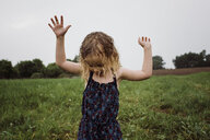 Wet girl with arms raised standing on grassy field against sky at park during rainy season - CAVF49619