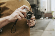Midsection of man holding camera while standing on city street - CAVF49646