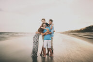 Happy siblings embracing while standing at beach against sky during sunset - CAVF49655