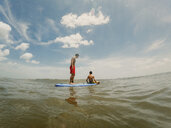 Shirtless brothers paddleboarding on sea against sky - CAVF49658