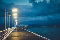 A half lit pier at sea during dusk - INGF01796