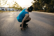 Man skateboarding on empty raos at sunset - JRFF01908