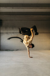 Man doing breakdance in urban concrete building, standing on hand - JRFF01911
