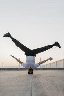 Man doing breakdance in urban concrete building, standing on head - JRFF01917