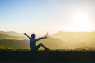 Spain, Canary Islands, Gran Canaria, back view of happy man watching mountain landscape at sunset - KIJF02063
