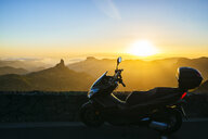 Spain, Canary Islands, Gran Canaria, parked motor scooter in front of mountainscape at sunset - KIJF02066