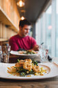 Businessman having lunch at a restaurant - KKAF02435