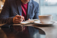 Businessman sitting in restaurant drinking coffee and checking his notebook - KKAF02441