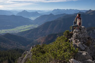 Germany, Upper Bavaria, Aschau, hiker sitting on viewpoint at Kampenwand - HAMF00513