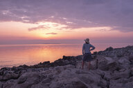 Croatia, Istria, Losinj, woman standing on rocky coast at sunset - HAMF00518