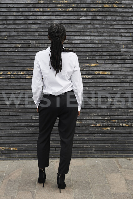 Back view of businesswoman with dreadlocks wearing white shirt and black trousers - IGGF00670