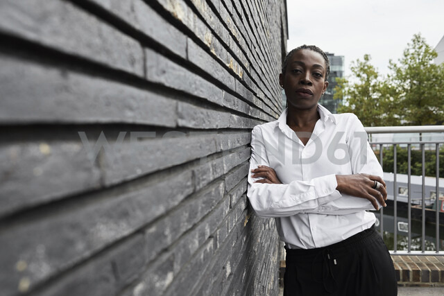 Portrait of serious businesswoman leaning against wall - IGGF00673