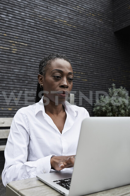 Portrait of businesswoman sitting on  terrace of a coffee shop working on laptop - IGGF00679
