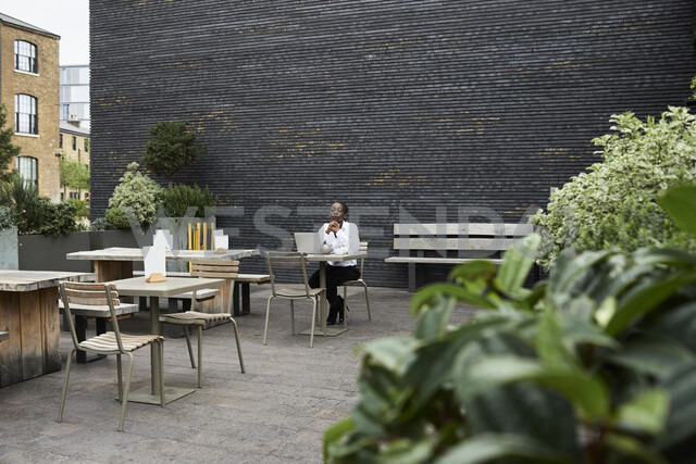 Pensive businesswoman sitting with laptop on roof terrace of a coffee shop - IGG00682