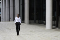 Businesswoman wearing white shirt and black trousers walking in front of a modern office building - IGGF00688