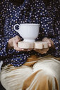 Woman's hands holding wooden board with white tea cup, close-up - ALBF00649