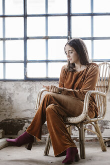 Fashionable young woman sitting on basket-chair in a loft - ALBF00658
