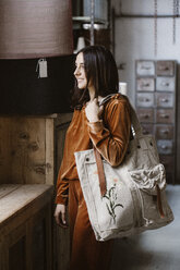 Smiling fashionable young woman with big shopping bag in a loft - ALBF00661