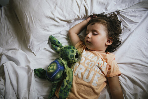Baby girl sleeping on bed with t-shirt message 'Dreams do come true' - GEMF02423