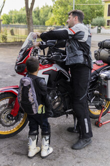 Father and son preparing for a motorbike trip - FBAF00125