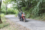 Father and son on a motorbike trip on a country road - FBAF00131