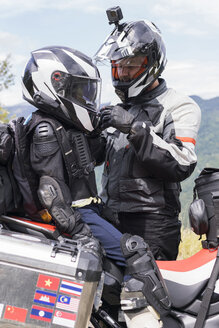 Father and son having a break during a motorbike trip - FBAF00143