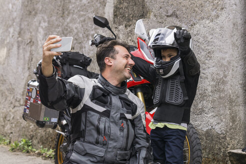 Happy father and son taking a selfie on a motorbike trip - FBAF00149
