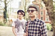 Teenage boy wearing sunglasses in park - LUXF01197